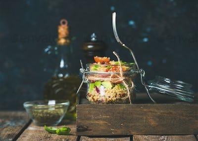 Healthy homemade jar quinoa salad with sun-dried tomatoes, avocado, basil