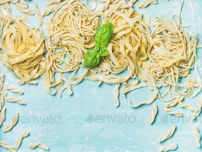 Various homemade fresh Italian pasta with flour and  basil