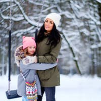 Little girl with her mother outdoor in a snow