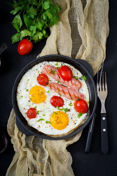 English breakfast - fried egg,  tomatoes and sausage. Top view. Flat lay