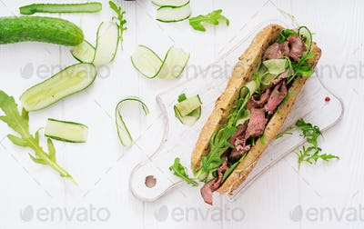 Sandwich of whole wheat bread with roast beef, cucumber and arugula. Top view. Flat lay