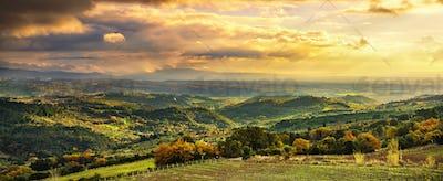 Maremma sunset panorama. Countryside, hills and sea on horizon.