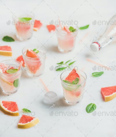 Cold refreshing summer alcohol cocktail with fresh grapefruit in glasses