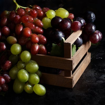 White, red and blue grapes on a dark Background