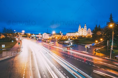Minsk, Belarus. Night Traffic On Illuminated Street And  Cathedr