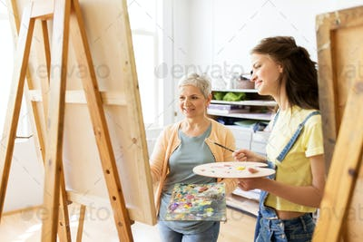 women with easels and palettes at art school