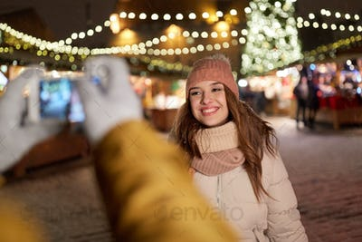 happy woman posing for smartphone at christmas