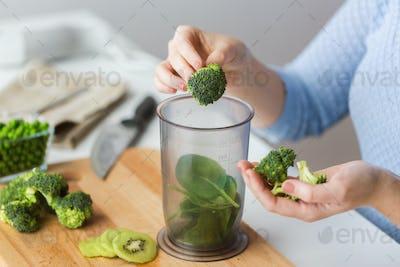 woman hand adding broccoli to measuring cup