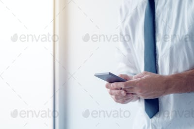 Businessman texting on mobile phone