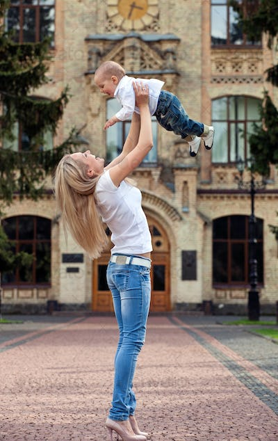 Happy young woman lifting her son high up outdoors