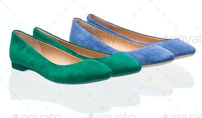 Pairs of green and blue pumps over white