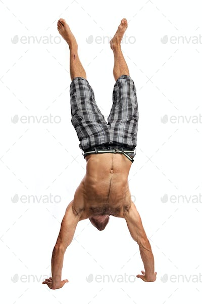 Young muscular man handwalking over white background