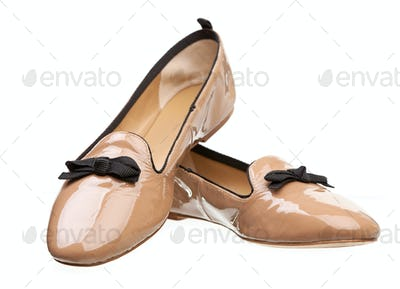 Pair of beige female shoes over white background