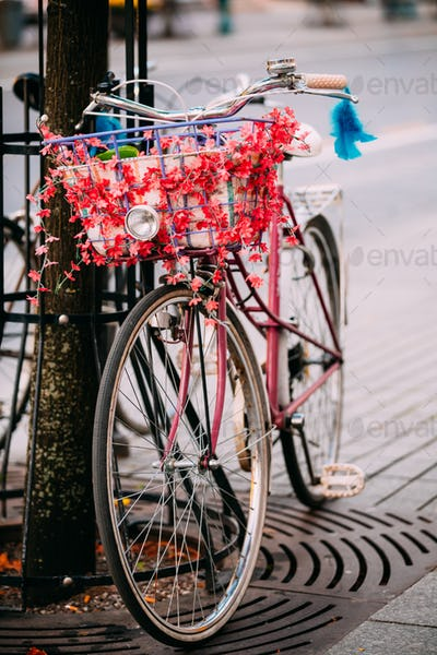 Female Bicycle Equipped Basket With Decorative Flowers Parked In