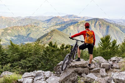 Mountain biker looking at view on bike trail in autumn mountains