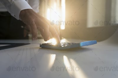 Hand of a businessman using a desk calculator