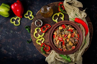 Roast chicken liver with vegetables on wooden background. Flat lay. Top view