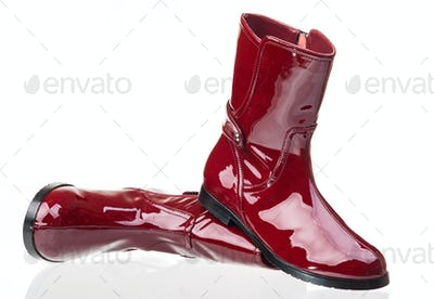 Pair of red patent leather female boots over white