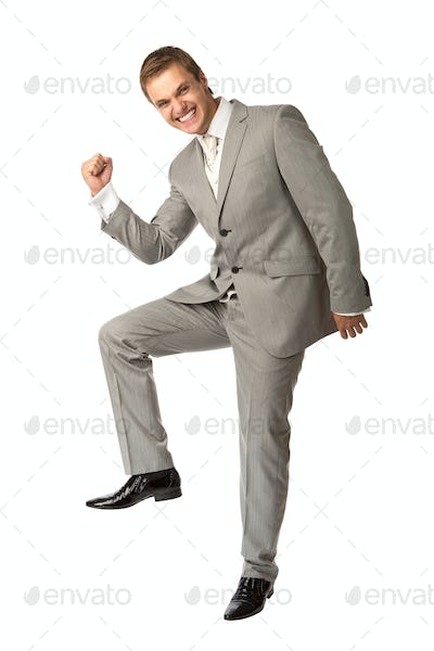 Cute young guy in suit clenching his fist in triumph