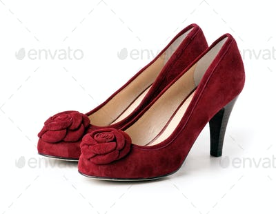 Pair of red suede female shoes over white