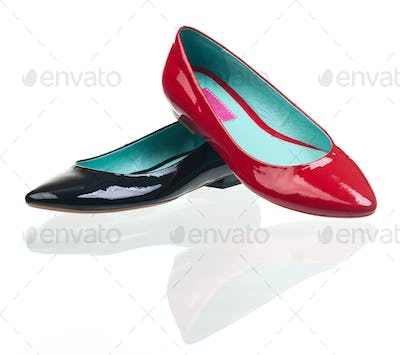Black and red patent leather pumps over white