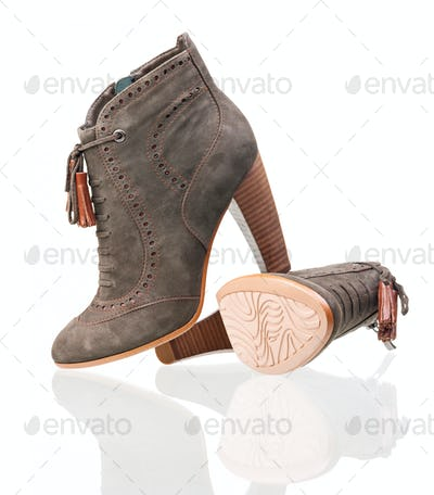 Pair of suede high heels boots over white