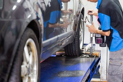 A mechanic fixing a wheel alignment devise onto the wheel of a vehicle.