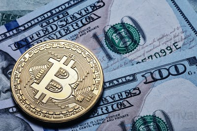 Gold bitcoin on hundred dollar bills