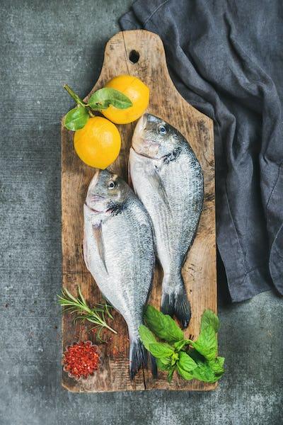 Uncooked sea bream or dorado fish with lemon, herbs, spices