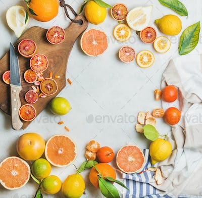 Citrus fruits slices over grey marble background, top view