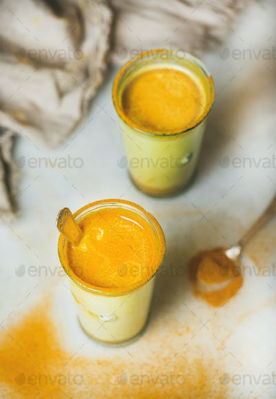 Golden milk with turmeric powder in glasses, natural flu remedy