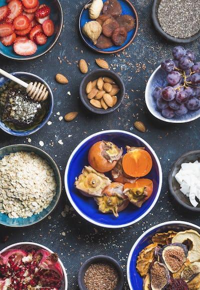 Ingredients in bowls for healthy breakfast over dark blue background