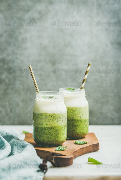 Ombre layered green smoothies with mint in jars with straws