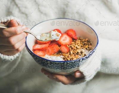 Healthy breakfast yogurt, granola, strawberry bowl in woman's hands