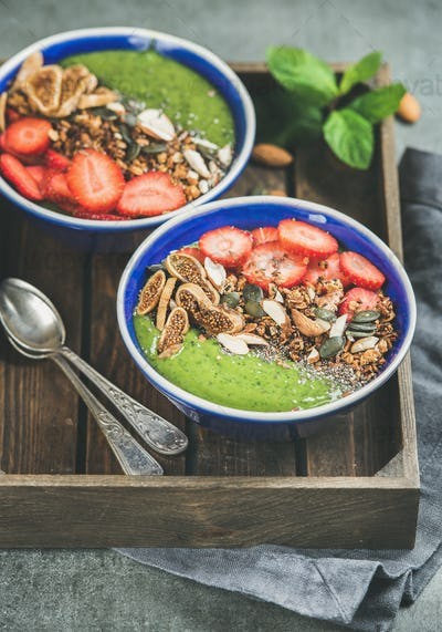 Green smoothie breakfast bowls with seeds, nuts, fruit and berries