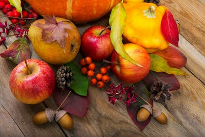 Fall background with yellow squash, apples, pear, colorful leave