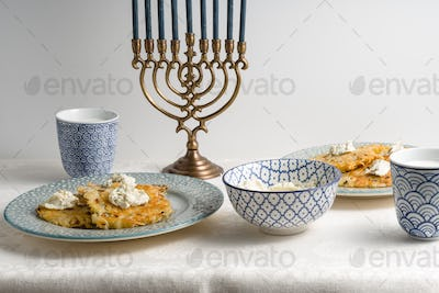 Latkes on a plate, Hanukkah, cups with milk on a white tablecloth