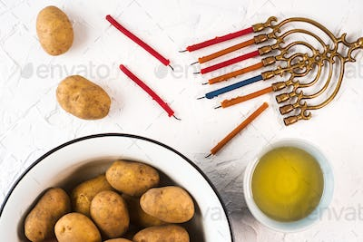 Hanukkah, olive oil and potatoes on a white background