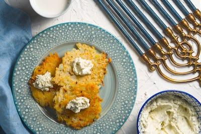 Latkes and curd cheese on a plate and on a blue napkin, chanukia