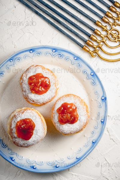 Donuts with jam on a plate with a blue rim and Hanukkah closeup