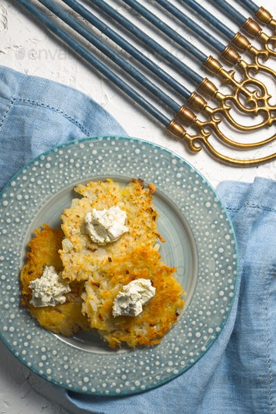 Latkes and curd cheese on a plate, Hanukkah close-up