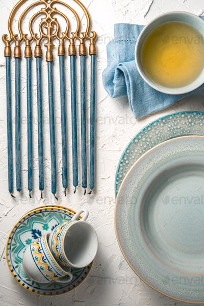 Hanukkah with candles, plates, butter in a bowl and blue napkin top view
