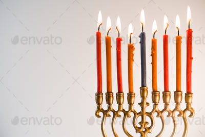 Brass hanukiya with lighted candles close-up