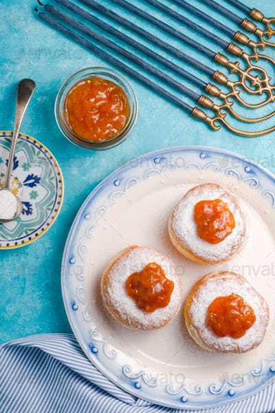 Donuts with jam on a plate and Hanukkah on a turquoise table