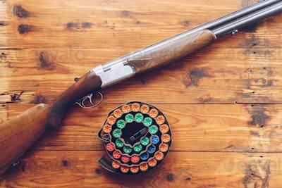 Hunting equipment. Shotgun and hunting cartridges  on wooden tab