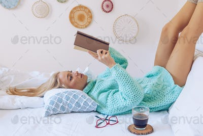 Young woman lying in bed while reading a book