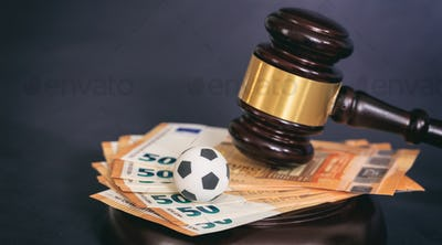 Law gavel, soccer ball and euros on black background