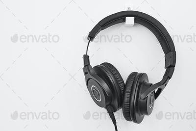 Headphone hanging on a white wall. Music background. Audio equipment