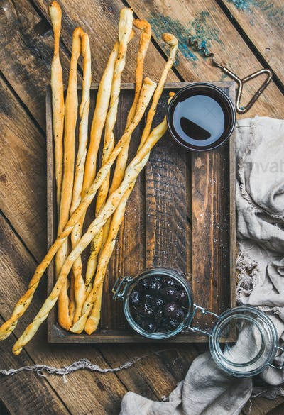 Grissini bread sticks, black olives, red wine in wooden tray