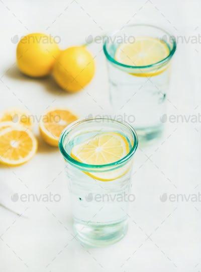 Detox lemon water in glasses served with fresh lemons